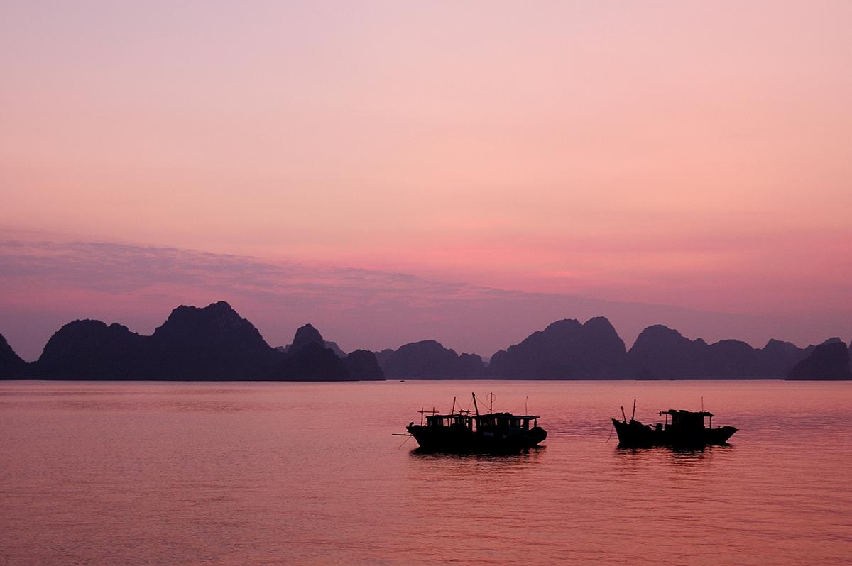 Bateaux au coucher de soleil sur la baie d'Halong