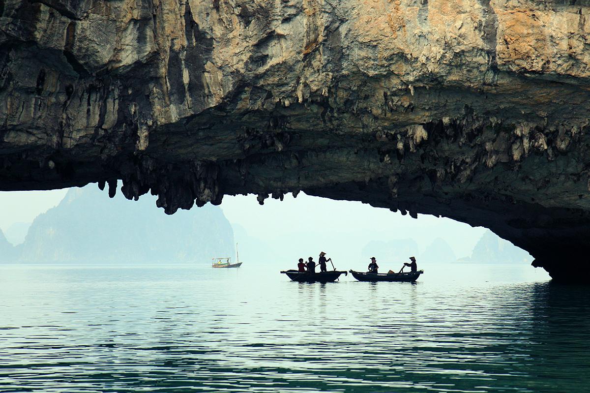 Des barques sous une grotte de la baie d'Halong