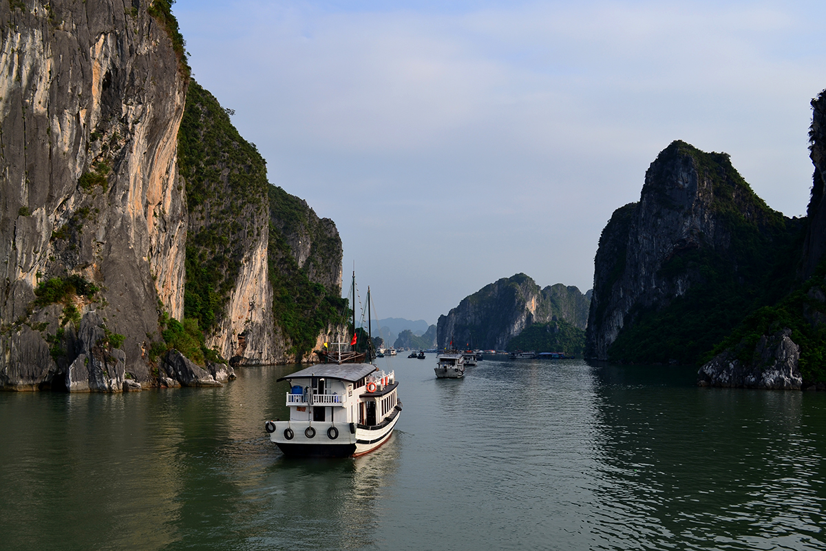Boat cruising through the mountains of the Halong Bay